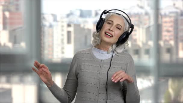 Starší žena poslouchá hudbu ve sluchátkách a těší.