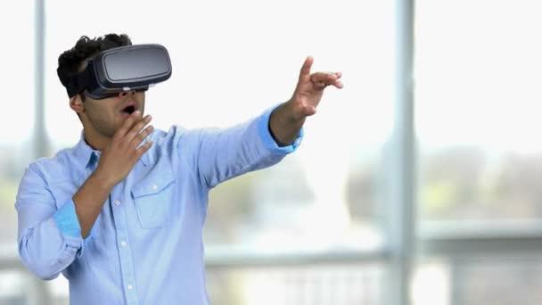 Erstaunte junge indische Mann trägt Virtual-Reality-Headset.
