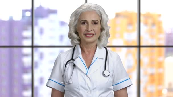 Portrait of a female doctor with grey hair wearing stethoscope.