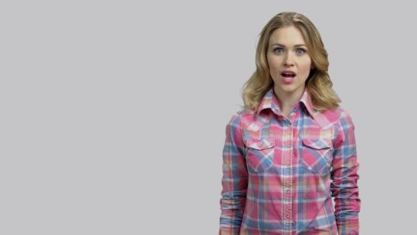 Schockierte junge blonde Frau zeigt Kopierraum mit hochgehaltenen Handflächen.