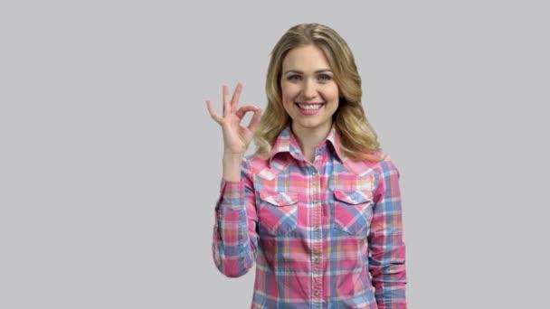 Šťastná mladá žena s blond vlasy ukazuje v pořádku gesto.