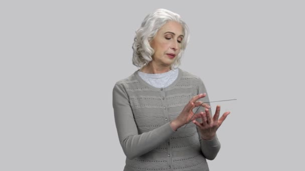 Happy old senior lady with glass mockup tablet pc.