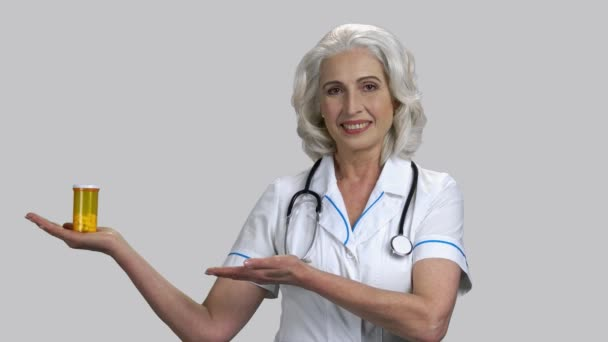 Happy old doctor showing can of pills with her palms up.