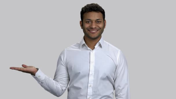 Happy young hindu man pointing at his empty palm for copyspace.