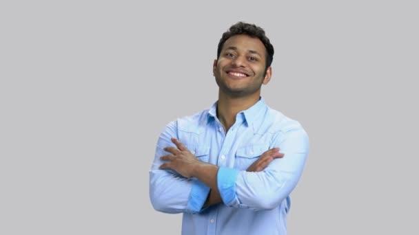 Portrét veselého muže s tmavou pletí, který si založil ruce.