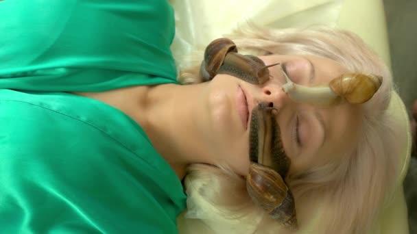 Terapeutičtí šneci plazící se po ženské tváři.