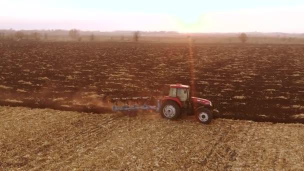Piros modern traktor szántás talaj vetés előtt.