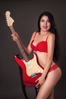 Sexy young brunette in red lingerie holding electric guitar in studio