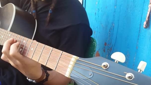 Kytarista ruce hraje píseň na akustickou kytaru