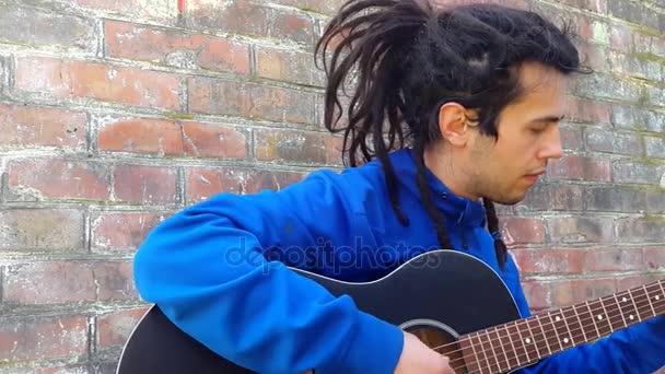 Mladý muž s dredy, hraje na akustickou kytaru na pozadí cihlová zeď