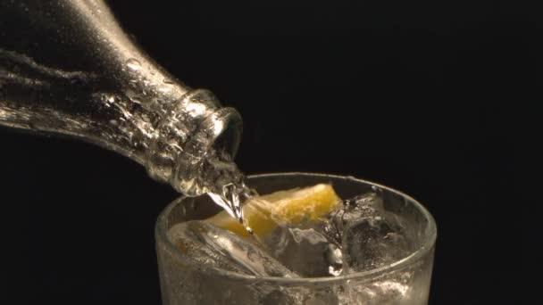 Friss víz ömlött egy pohár hideg jégkocka és citrom fröccsenő cseppek és buborékok lassú mozgás lövés 1000 fps fekete háttér