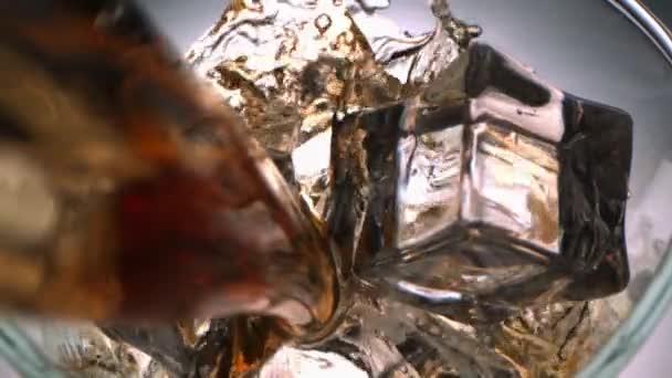 Pohled shora na Whiskey Pouring s proudem uvnitř sklenice s kostkami ledu s kamerou Dollying in