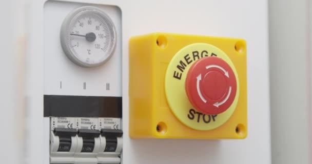Hand drückt Not-Aus-Taste auf der Systemsteuerung mit Elektrizitätsschalter