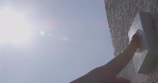 Türklingeln mit Schutzhandschuhen und ohne männliche und weibliche Finger mit Sonnenstrahlen und blauem Himmel - ein Konzept des Covid-19 Coronavirus-Schutzes
