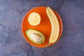 Tropical fruits on orange plate