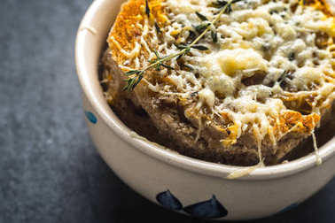 French onion soup in a ceramic bowl on a gray stone