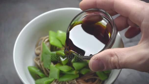 Sojasauce in Buchweizen-Nudeln mit Bohnen gießen