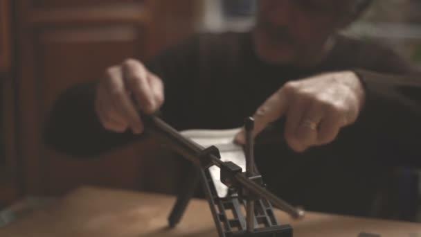 Muž v hnědé sako se zostří kuchyňský nůž částečné rozostření videa