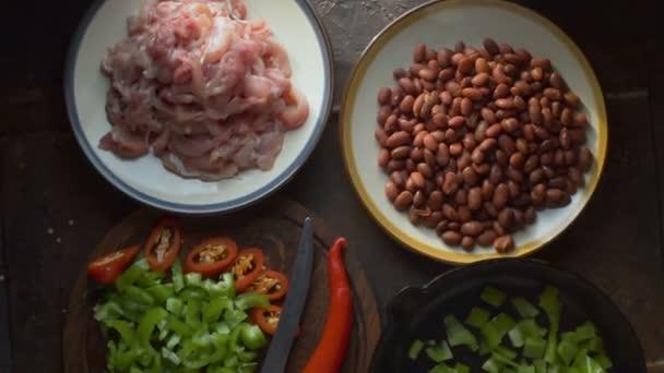 Pohled shora na kousky kuřecího, fazole a papriky na stole. Video