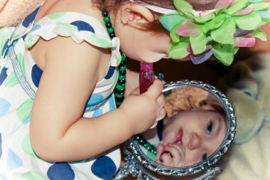 Beautiful little girl looking in the mirror and paints her lips. Selective focus.