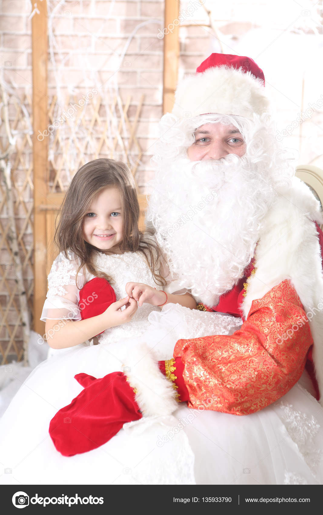 4c2f77d790a Santa Claus in a red cap holding a baby on her knees — Stock Photo ...