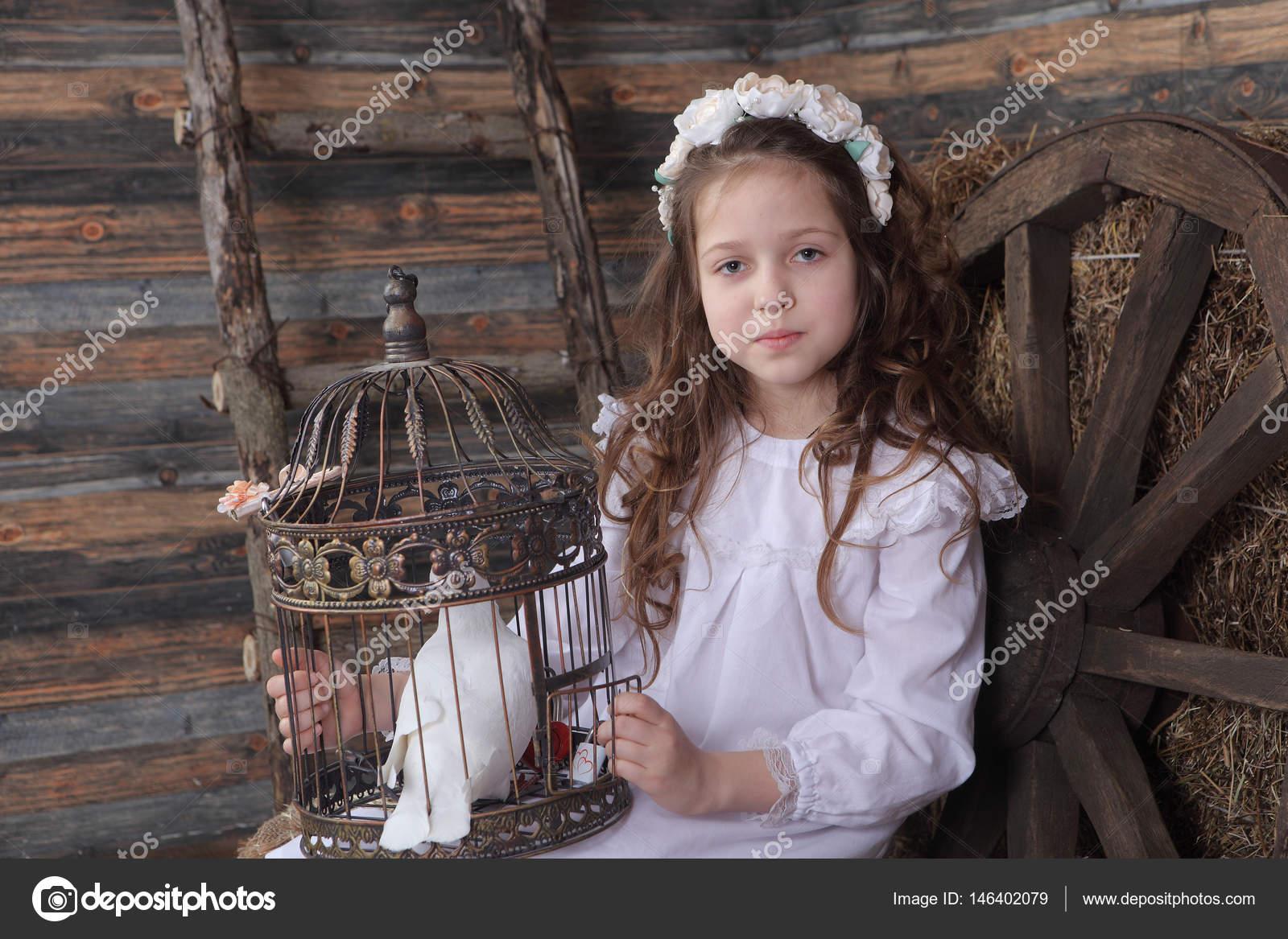 80f4203fcf40 Κορίτσι με ένα στεφάνι και ένα λευκό φόρεμα που κρατά ένα κλουβί με έναν  ζωντανό λευκό dov — Εικόνα από ...
