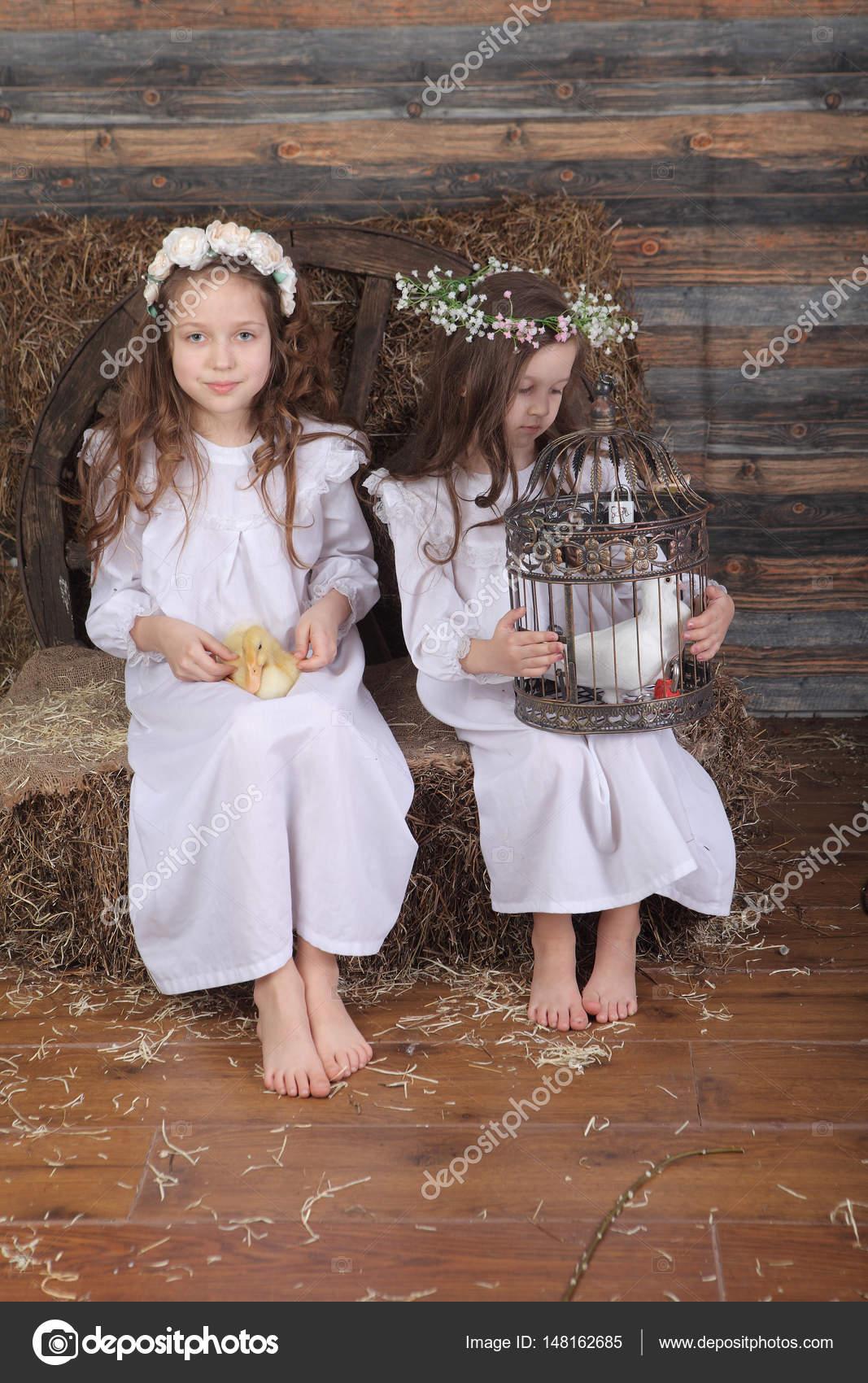 22272dc0f62f Δύο κορίτσια φίλες διεξάγουμε μια ζωντανή πάπια και ένα κλουβί με ένα–  εικόνα αρχείου