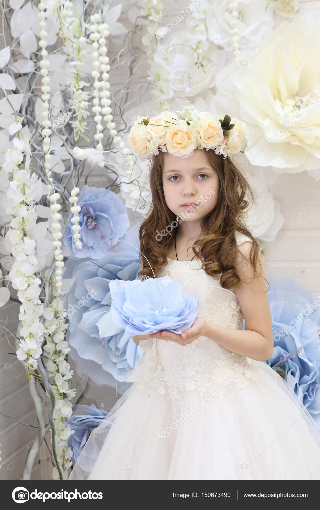 Jeune Fille Dans Une Couronne De Fleurs Et Une Robe Blanche Tenant