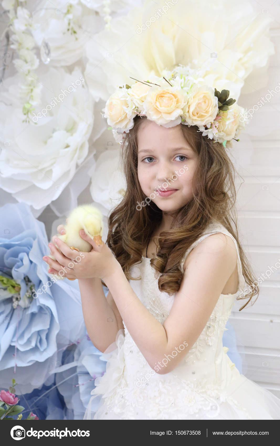 673f54a7a942 Κορίτσι με ένα στεφάνι και ένα λευκό φόρεμα κατέχει μια ζωντανή πάπια–  εικόνα αρχείου
