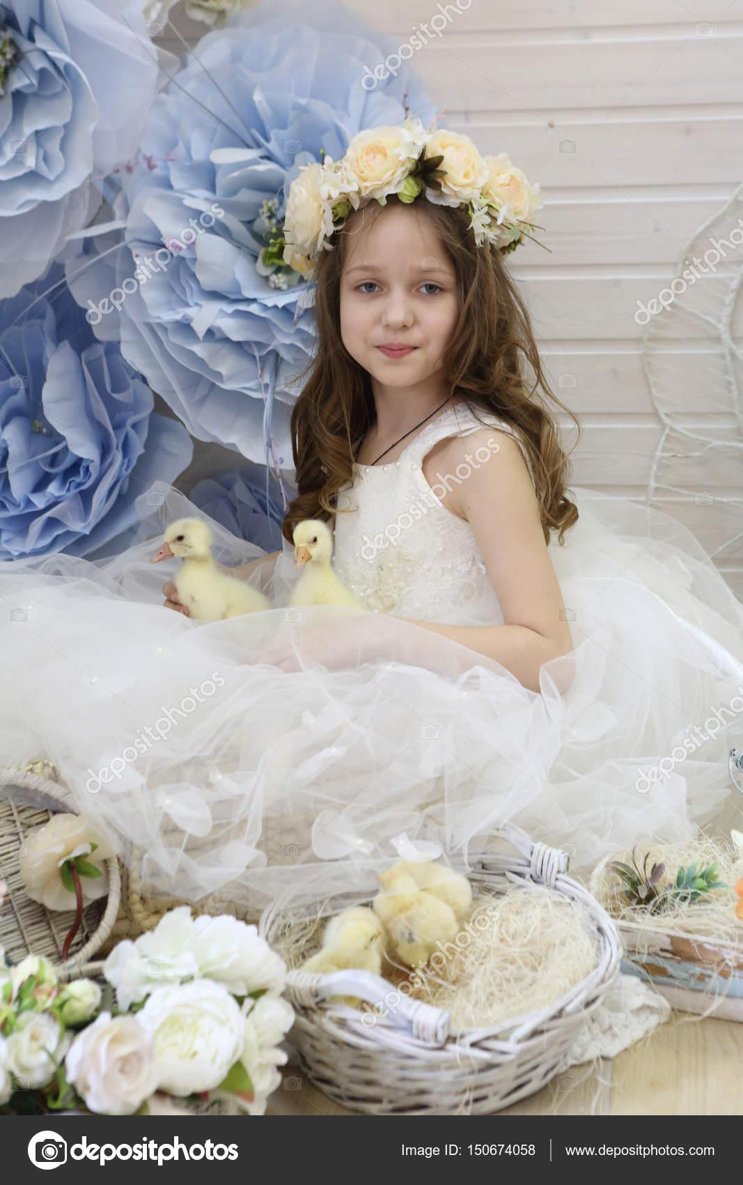 0513cfb95c3b Κορίτσι με ένα στεφάνι και ένα λευκό φόρεμα που παίζει με μια ζωντανή πάπια–  εικόνα αρχείου
