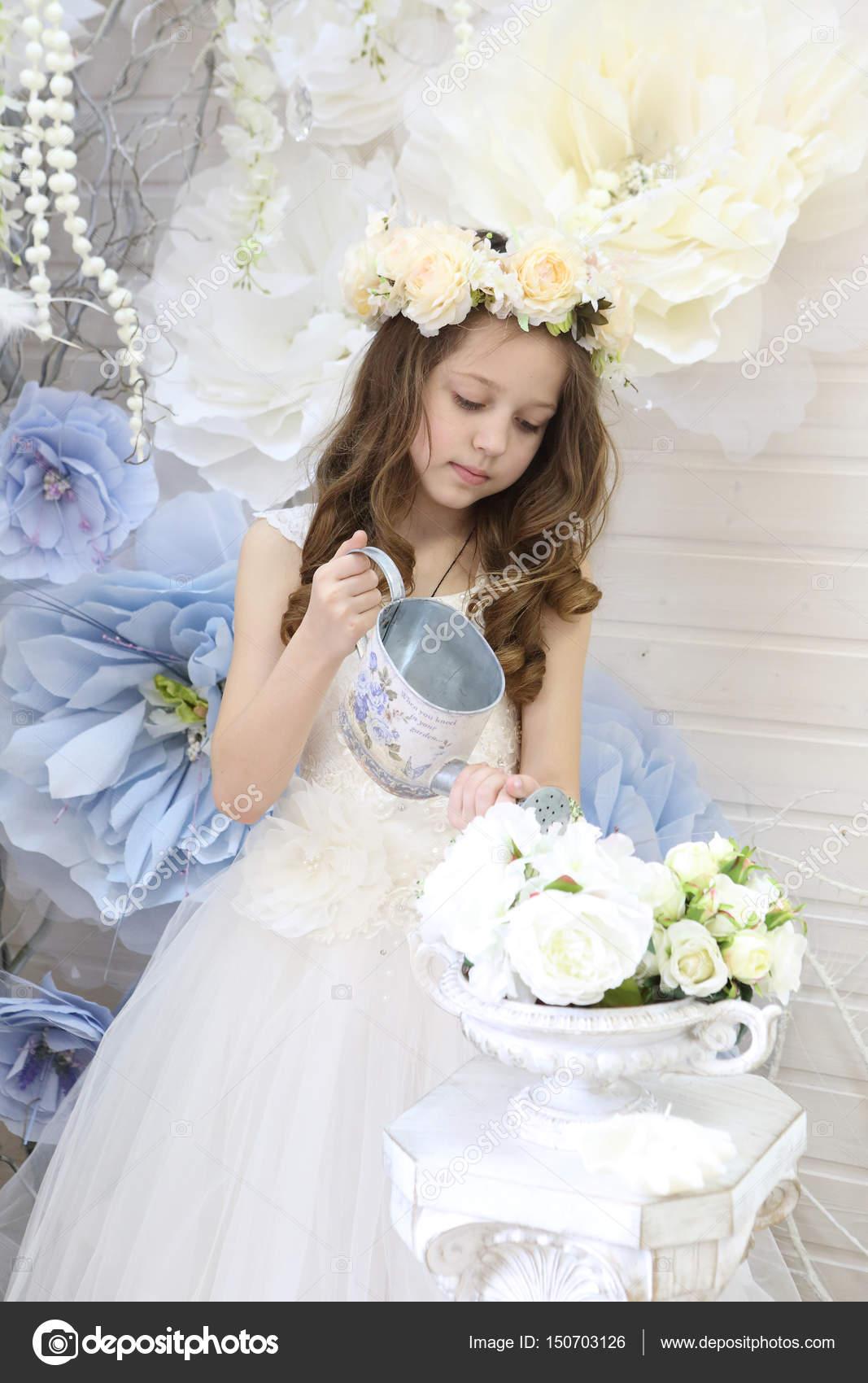 e3aea87706f2 Κορίτσι με μακριά μαλλιά με ένα στεφάνι και ένα λευκό φόρεμα πότισμα  λουλουδιών από ένα πότισμα ca — Εικόνα από DmZo