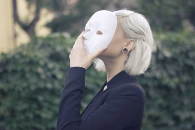 Young blond woman taking off a mask. Pretending to be someone else concept. outdoors.