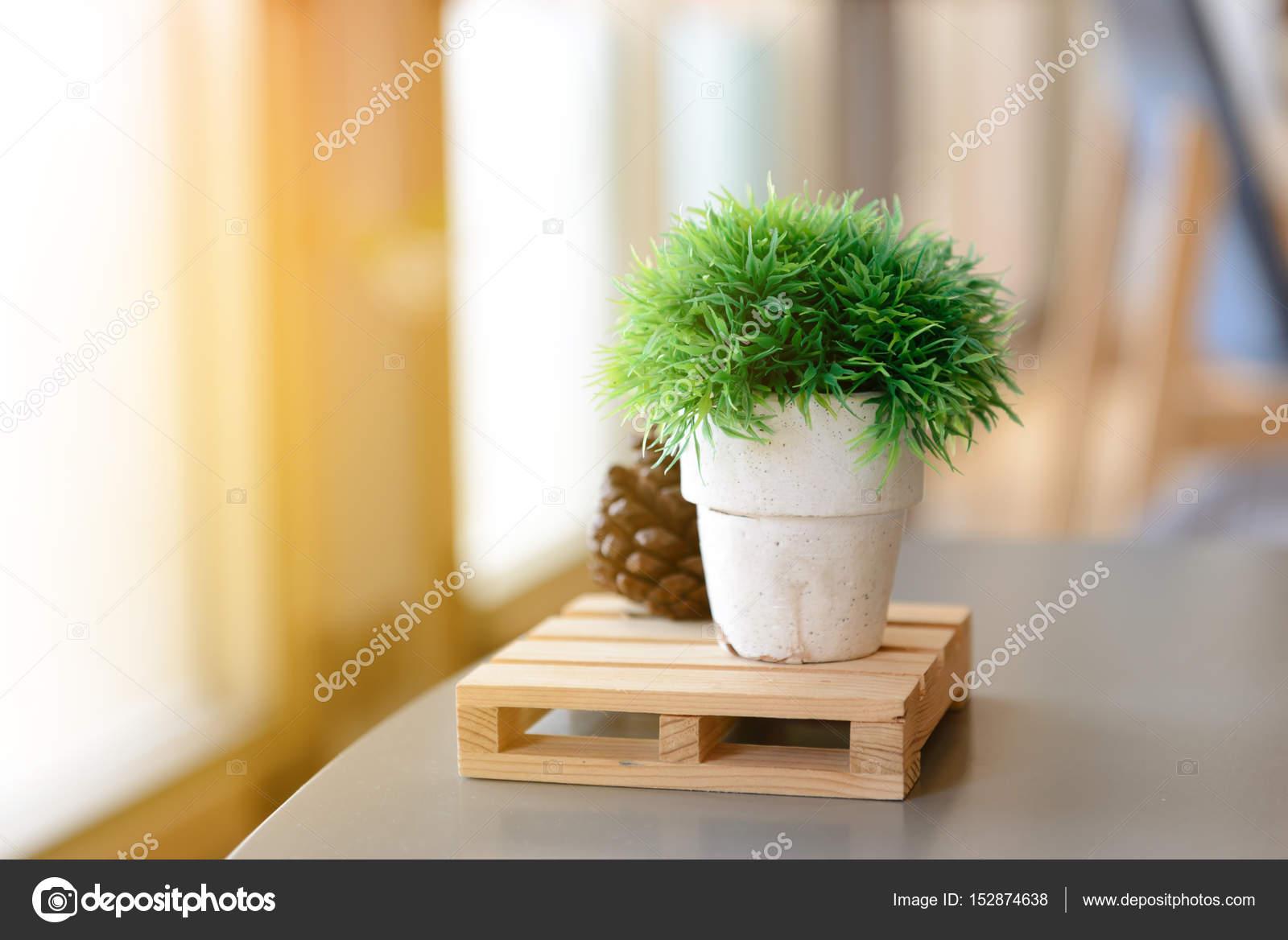 Kleine kunstmatige bomen of kunstgras in vaas op tafel met kopie