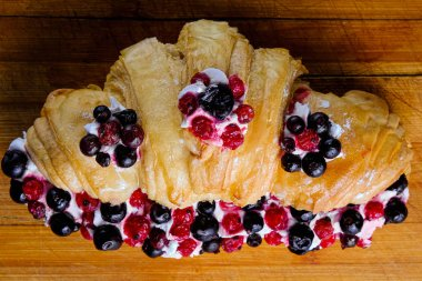 Croissant sandwiche with berries on a wooden background