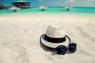 Sunglasses and hat on white sand beach at tropical island