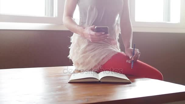 Hands of woman writing in her diary and using a smart phone