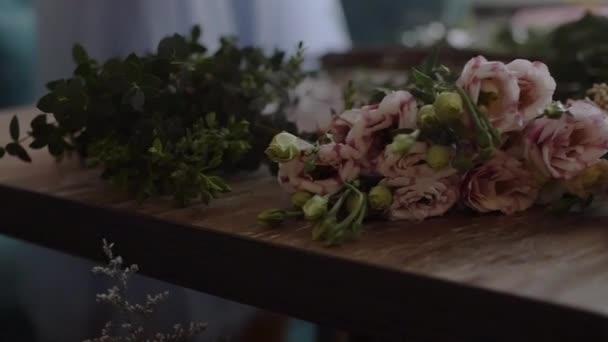 Květinářství připraví kytici květin k zákazníkům v lásce. Květinový design, květinové umění, vytvoření květinových aranžmá z řezaných květin, foliages, bylinky, okrasné trávy, rostlinné materiály.