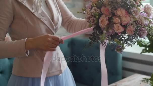 Květinářství připraví kytici květin k zákazníkům v lásce. Květinový design, květinové umění, vytvoření květinových aranžmá z řezaných květin, foliages, bylinky, okrasné trávy, rostlinné materiály
