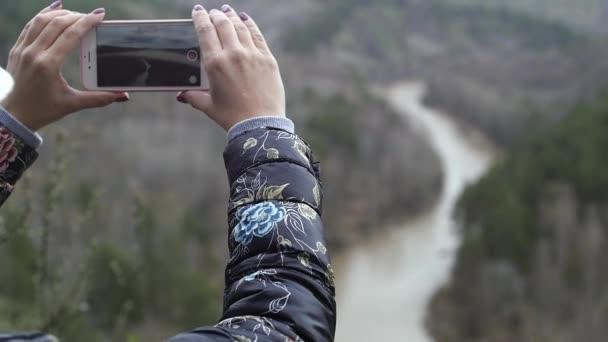 Pretty woman taking photo with smart phone at mountain peak. Marvelous daybreak.