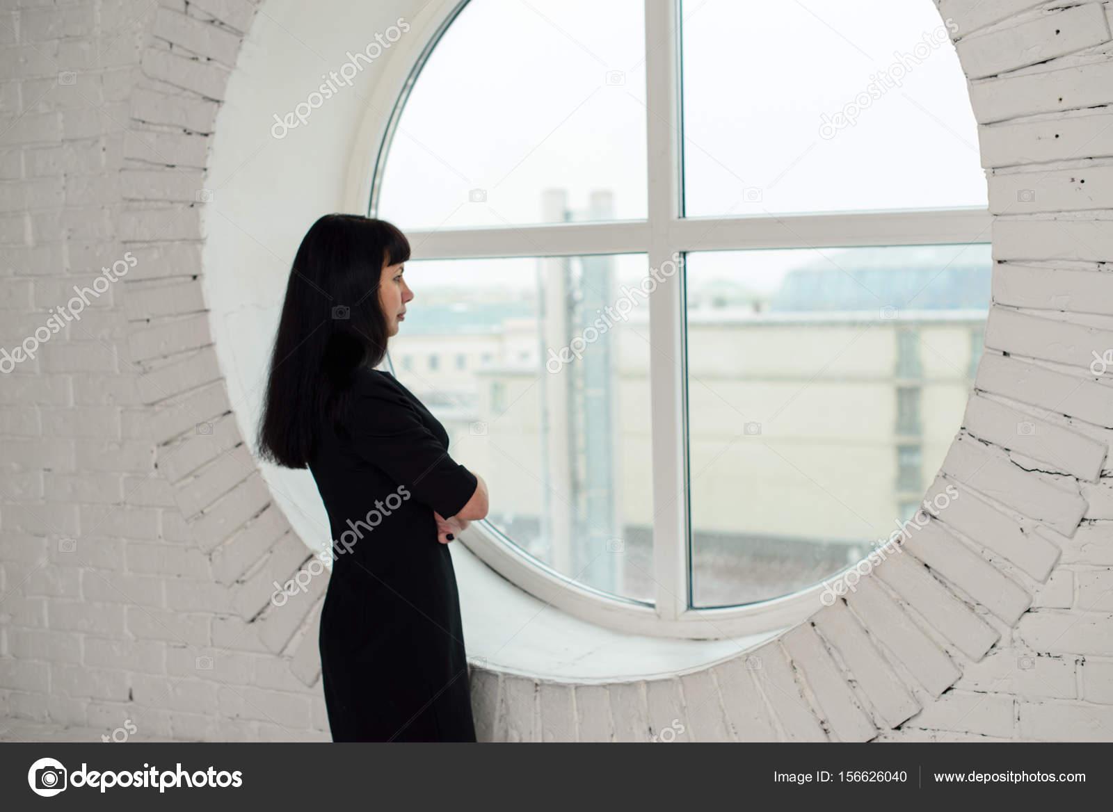 une fille dans une robe noire est debout devant une grande fen tre dans le bureau photographie. Black Bedroom Furniture Sets. Home Design Ideas