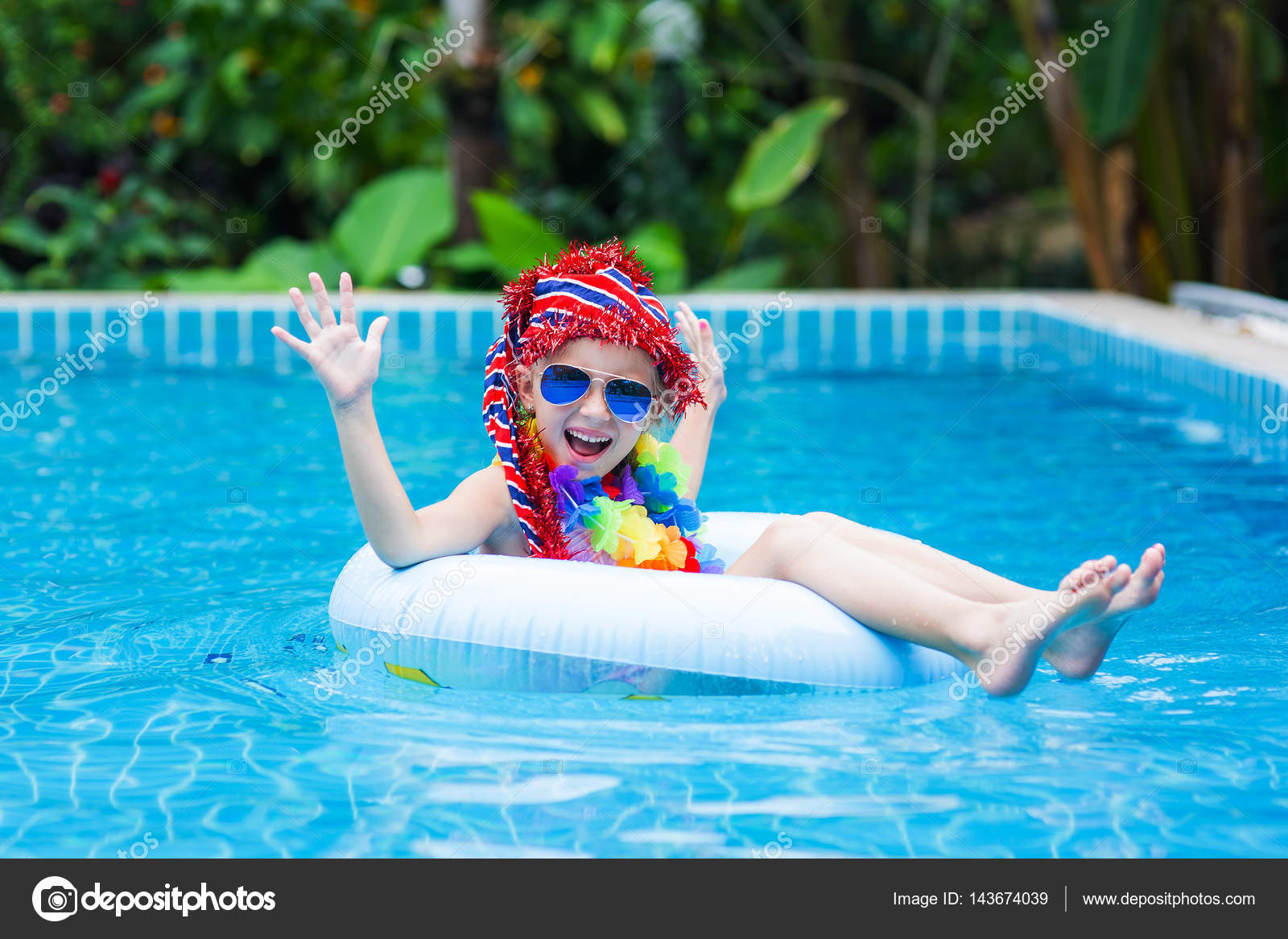 0615cc2000c4 Little girl in sunglasses and red cap floating on the circle in the pool at  a