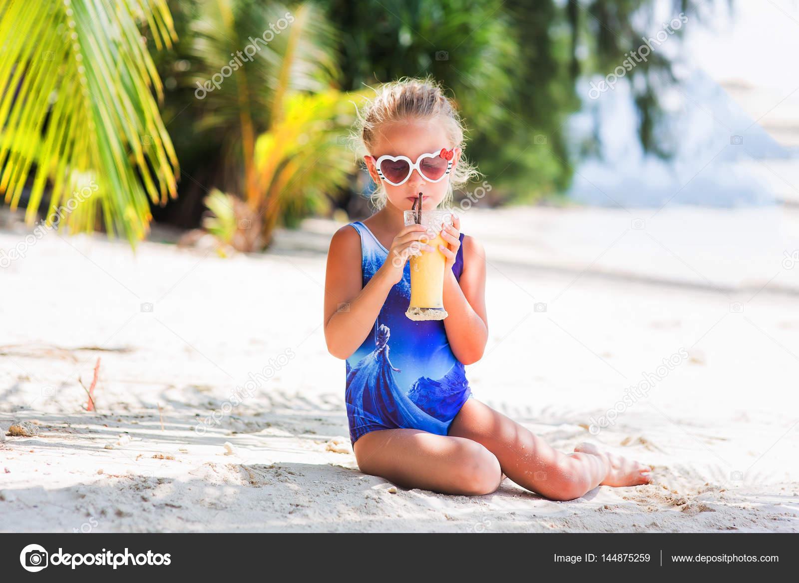 kleine s e m dchen am strand im badeanzug sonnenbrille sitzen unter einer palme exotischen. Black Bedroom Furniture Sets. Home Design Ideas