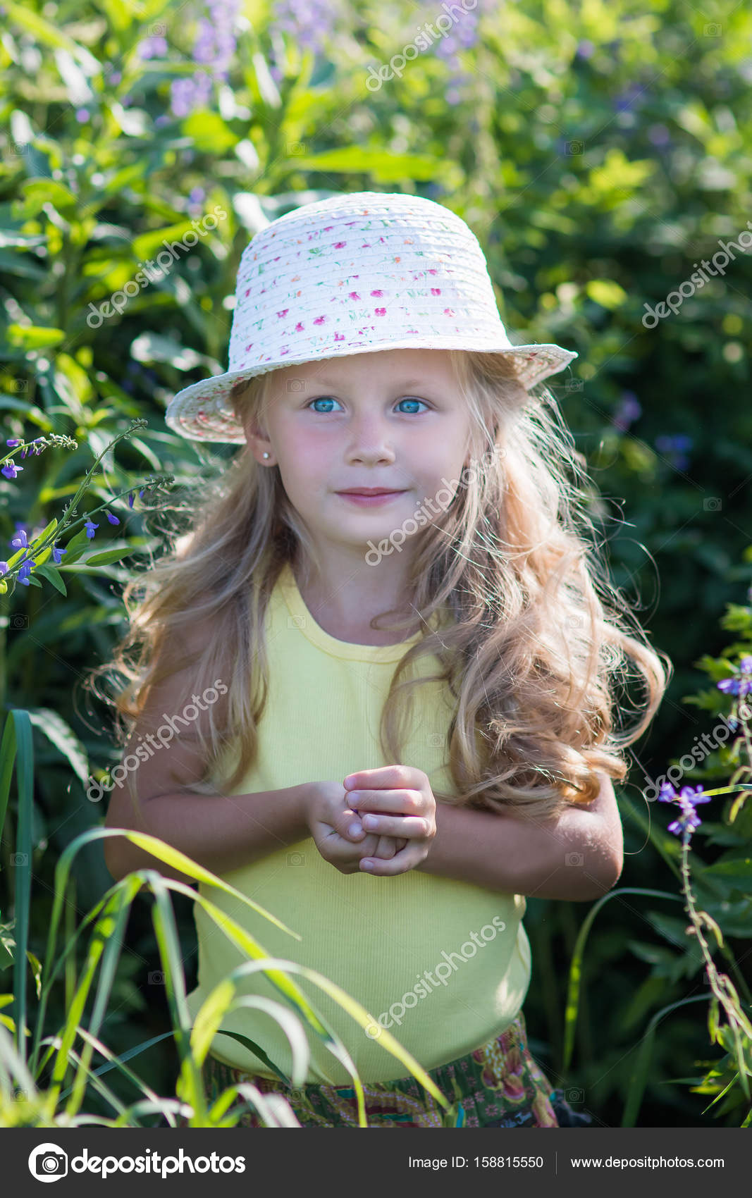smiling cute baby girl 4-5 year old holding flower wearing big hat