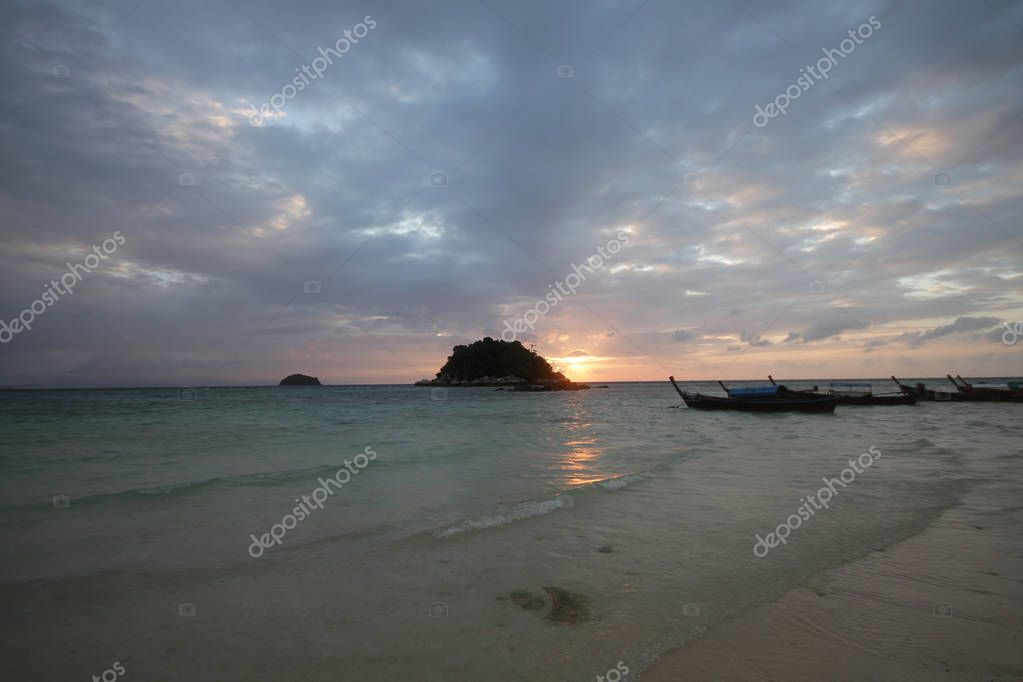 rock shadow in front of Golden rays of dawn light shining through idyllic beach and ocean, backgrounds, commercial advertisement