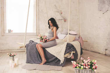 happy pregnant woman in grey dress sitting on bed
