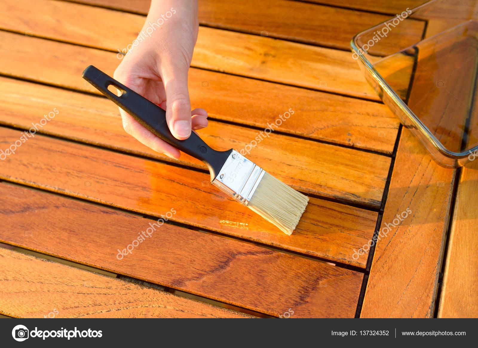 main tenant un pinceau, appliquez la peinture de vernis sur une ...
