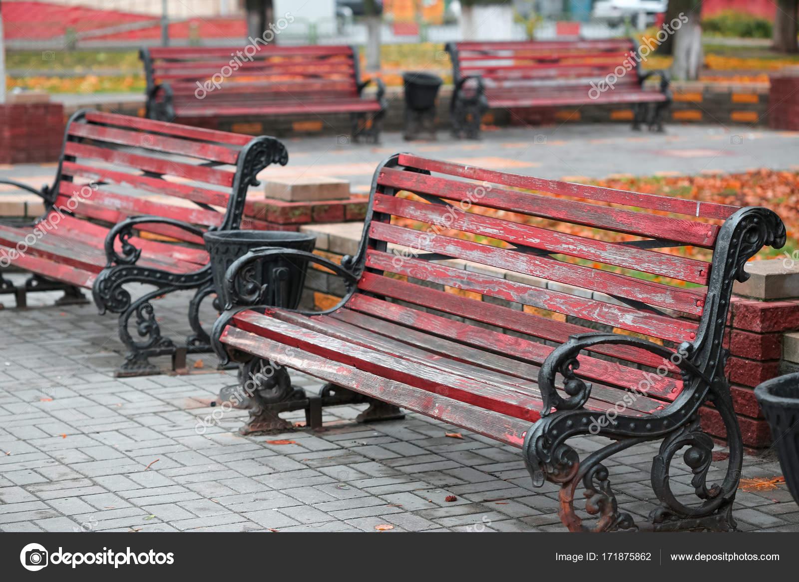 деревянные скамейки на чугунная станина в городском парке