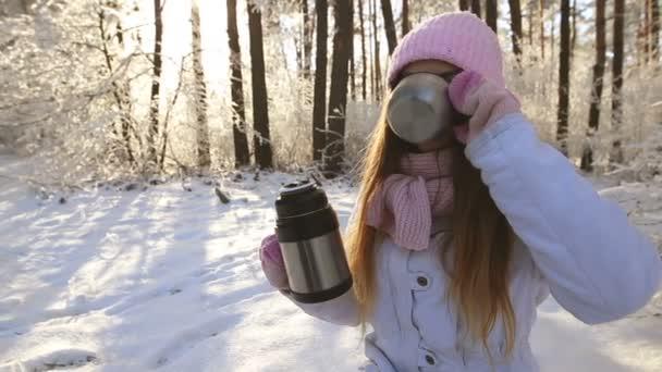 krásná dívka v růžové čepici a rukavice v zimě zasněžené lesní pití čaje