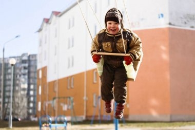 child on a swing in the playground in spring 2020