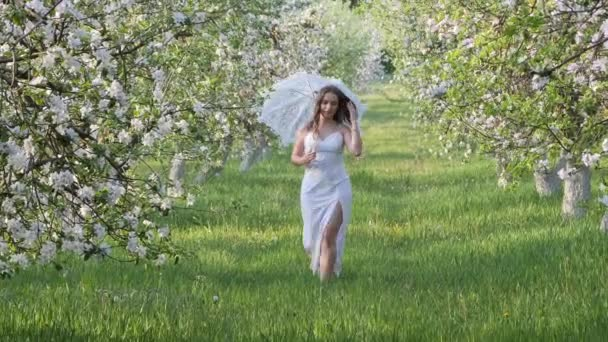 girl with a white umbrella in blooming apple trees in the garden 2020